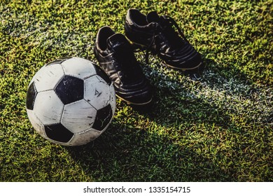 soccer ball and boots on green grass