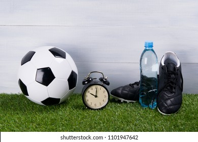 soccer ball, a bottle of water, black boots and an alarm clock stand on the grass, on a gray background