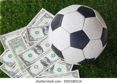 soccer ball with dollar bill on grass background