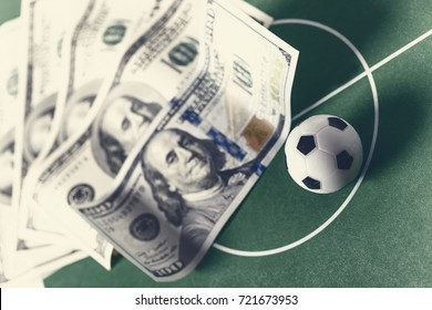 soccer ball and dollars on the football field. betting odds concept.Toned