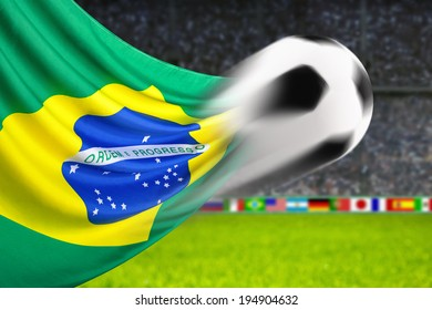 Soccer ball in fast motion in front of the Brazilian flag waving in a spiffy way in a football arena