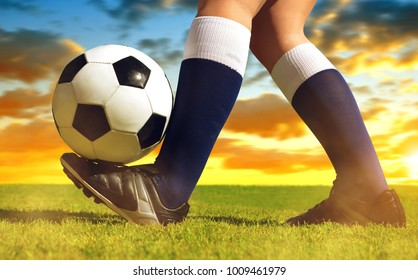 Soccer ball with feet player on the football field at sunset.