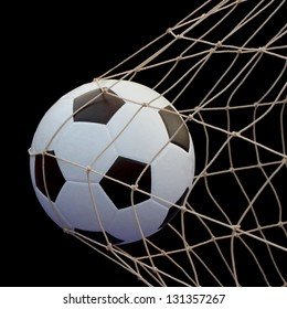 Soccer ball flying in the net isolated on Black background