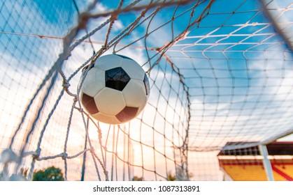 Soccer ball flying in the net; scored goal, win, success