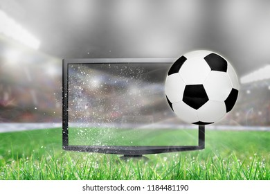 Soccer ball flying out of shattering TV screen in stadium with copy space. Concept of realistic 3D or 4D TV, virtual reality VR or computer gaming.
