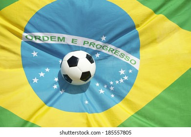 Soccer ball football flying into bright Brazilian flag background
