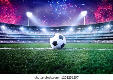 Soccer ball / football on green at stadium arena in night bright spotlights