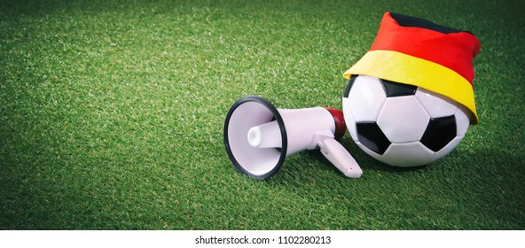Soccer ball with german fan cap and megaphone on the playing field