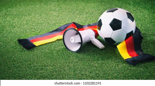 Soccer ball with german fan scarf and megaphone on playing ground