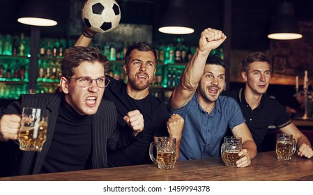 With soccer ball. It's a goal. Celebrating victory. Three sports fans in a bar watching football With beer in hands.