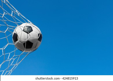 soccer ball in goal net with blue sky