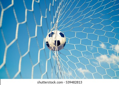 soccer ball in goal net with blue sky, retro vintage filter effect