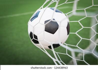 soccer ball in goal net with green grass