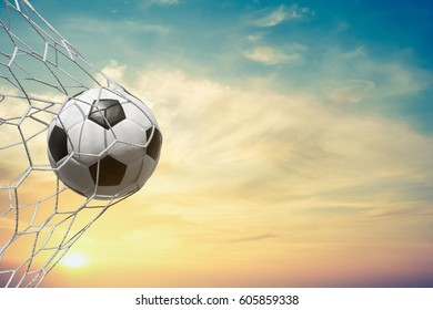 soccer ball in goal net with sun sky