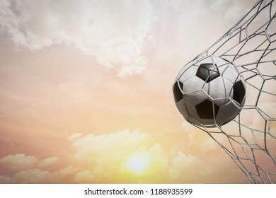 soccer ball in goal net with sunset