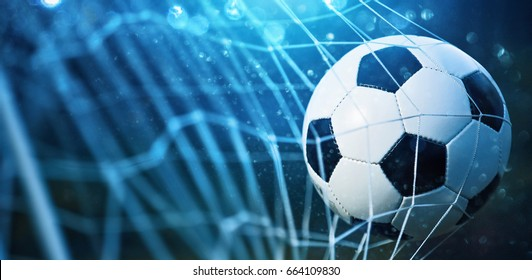 Photo of Soccer ball in goal on blue background