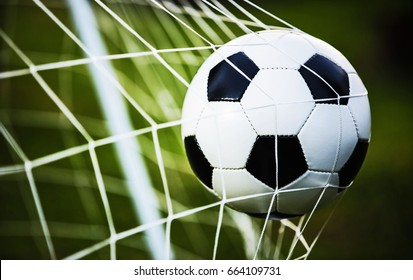 Soccer ball in goal on green grass