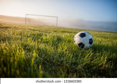 Soccer ball and goalpost in early morning light.