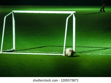 Soccer ball and goalpost on green soccer pitch at night