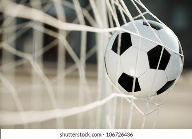 Soccer ball going into goal net ,selective focus