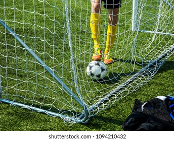 Soccer Ball in the grid of gate, the team player pulls the scored the ball out of the goal on green field