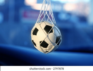 soccer ball hanging from a vintage car's mirror