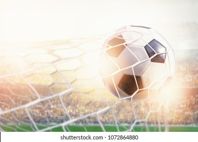 soccer ball hit the net against flare in the stadium during match,goal scoring concept