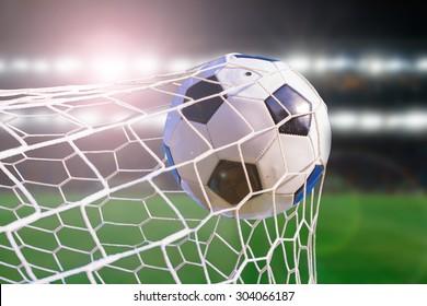 soccer ball hit the net,success goal concept on stadium light background