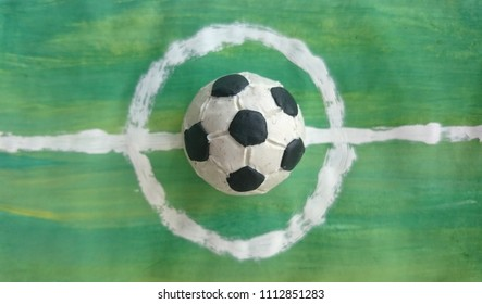 Soccer ball made of modelling clay on painted football field background