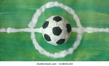 Soccer ball made of modelling clay on green painted background