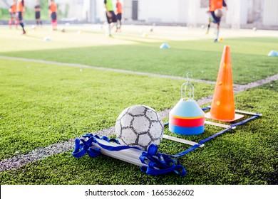 Soccer ball and marker cone with training equipment on green artificial turf with blurry player training background. Soccer Academy.