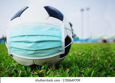 soccer ball with medical mask in the empty stadium. covid-19 spreading outbreak