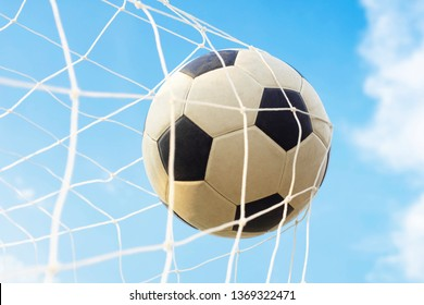 Soccer ball with net in goal and blue sky