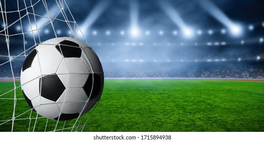 Soccer ball in the net, success goal concept on stadium light background.