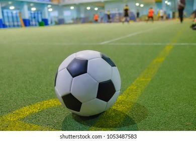 Soccer ball on a corner kick line on an artificial green grass field futsal mini football