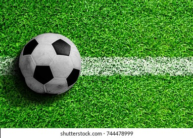 Soccer ball on field with white line marking ready for action. Line represents kickoff or sideline for throw in. Copy space.