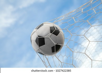 Soccer ball on goal with net and sky background, this photo can use for football, sport, goal, score, shoot and target of business concept