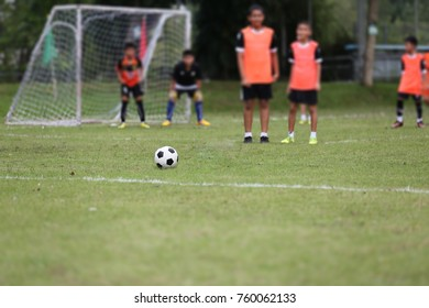 Soccer ball on the grass. The children stand in a wall, and a football goalkeeper as a backdrop. Soccer ball resting on the grass The children stand as a wall And a soccer goalie in the background.