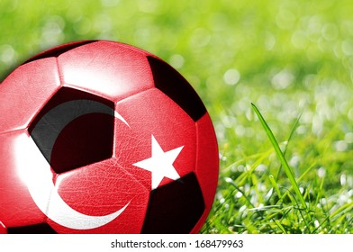 Soccer ball on grass with flag of Turkey painted on it