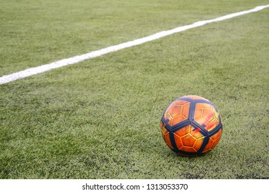Soccer ball on grass football field background with copy space.