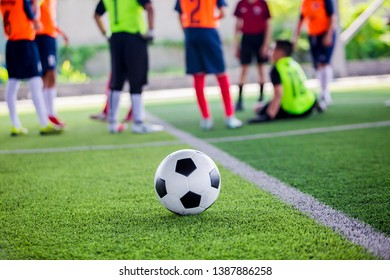 soccer ball on green artificial turf with blurry soccer players standing and sitting before training and start game.
