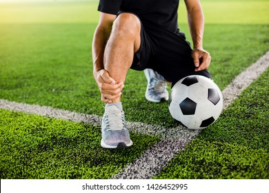 Soccer ball on green artificial turf with footballer is sitting and catch the ankle of the feet because of pain, soccer player was injured in the foot with pain during competition or practice.