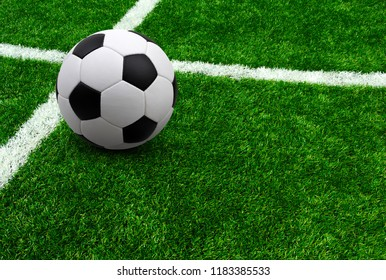 Soccer ball on green football field background with copy space