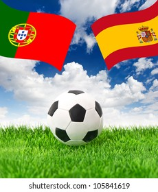 soccer ball on green grass and national flags of spain and portugal over dramatic blue sky