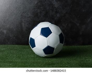 Soccer ball on green grass against black cement wall