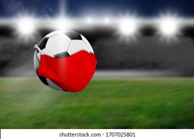 A soccer ball with a red face mask, in the background you can see the stadium and floodlights