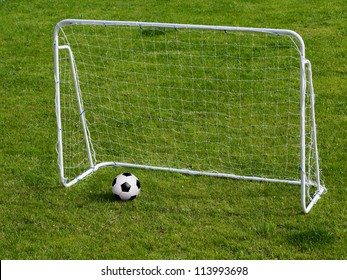 Soccer ball in small gates on green field