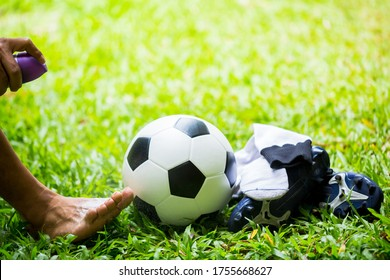 Soccer ball and sport shoes on green grass with spray suspension injuries. Sports doctor treating injured soccer player leg.