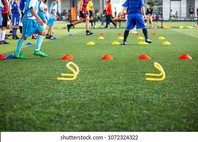 Soccer ball tactics on grass field with cone for  training children jump skill in Soccer academy
