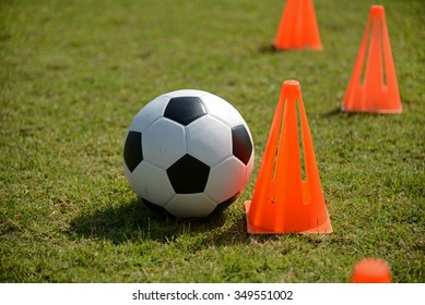 Soccer ball tactics on grass field with cone for training